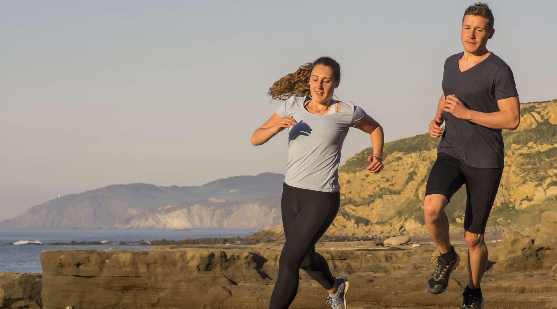 Man and woman running on single trail on coast of Azkorri beach